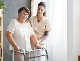 old woman assisted by her caregiver to walk