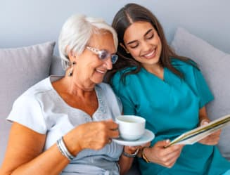 caregiver reading book while senior woman having a cup of coffee
