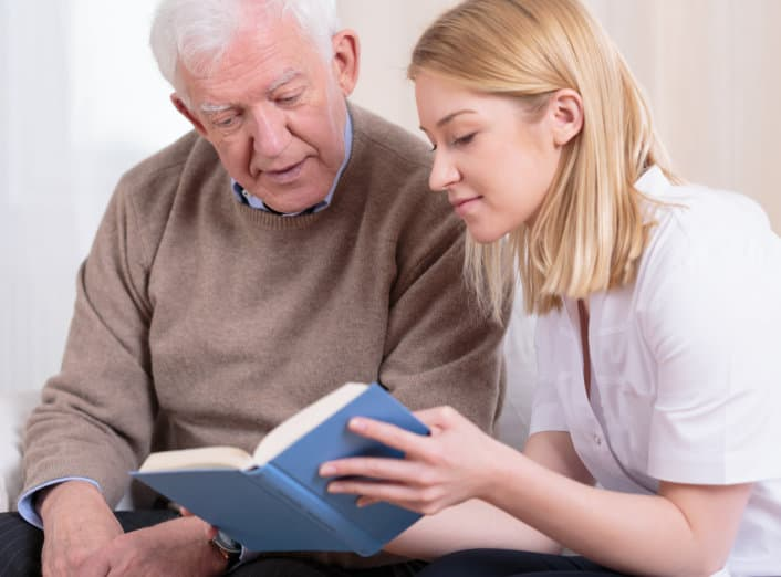 caregiver and her patient reading book together