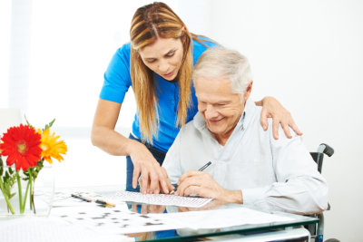 caregiver helping elderly man in writing