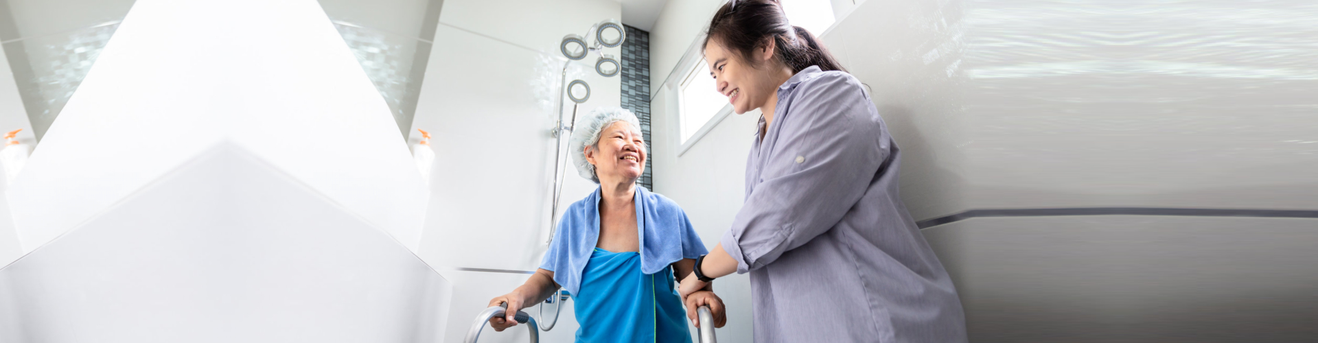 female care assistant service support senior woman taking a shower in bathroom